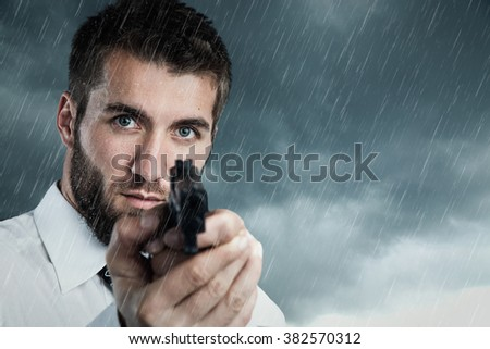 Attractive man with a beard is pointing at you with a gun