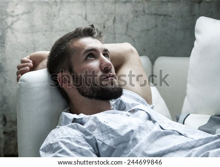 Attractive man with a beard is relaxing on a couch - stock photo