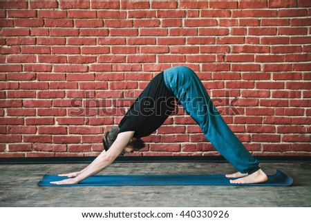 Attractive man with a beard wearing black T-shirt and blue trousers doing yoga downward dog position on blue matt at wall background, copy space, portrait, adho mukha svanasana - stock photo
