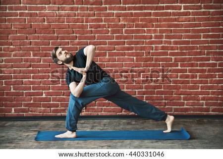 Attractive man with a beard wearing black T-shirt and blue trousers doing yoga position on blue matt at wall background, copy space, parivritta parshvakonasana asana with namaste mudra. - stock photo