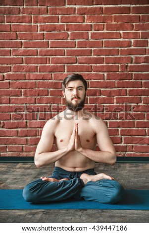 Attractive man with dark hair and beard wearing trousers doing yoga lotus position and sitting on blue matt at wall background, copy space, portrait, namaste mudra. - stock photo