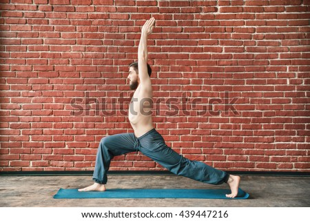 Attractive man with dark hair and beard wearing trousers doing yoga warrior position on blue matt at wall background, copy space, portrait, virabhadrasana asana. - stock photo