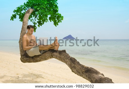 Attractive man with laptop seated in a tree on a tropical beach. - stock photo