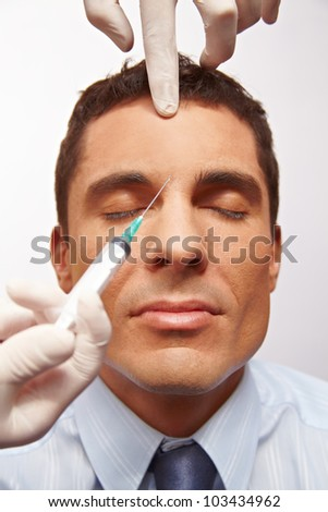 Attractive manager getting needle in forehead for wrinkle removal - stock photo