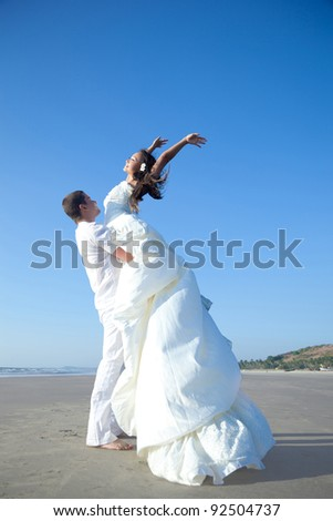 Attractive married couple are happy on the beach - stock photo