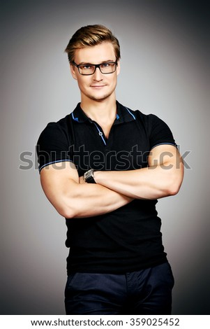 Attractive masculine young man in black clothes posing at studio over grey background. Men's beauty. - stock photo