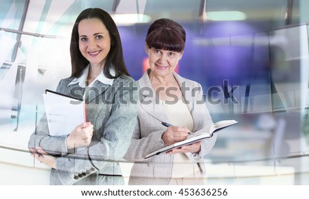 Attractive mature age woman and young businesswoman in office against of glass reflection  - stock photo