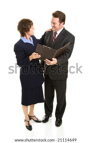 Attractive mature business man and woman going over a report.  Full body isolated on white. - stock photo