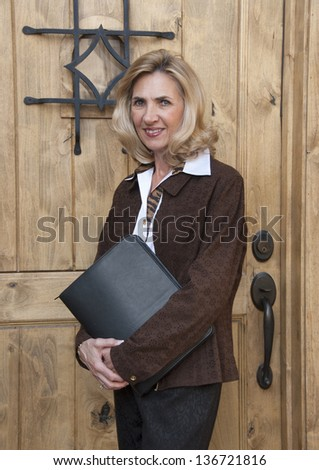 Attractive mature business woman standing outdoors in front of office door - stock photo