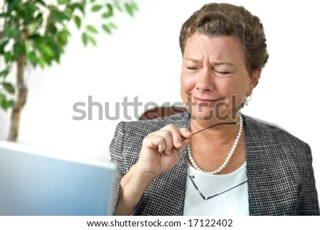 Attractive mature businesswoman looking with dismay, disbelief or amusement at her computer - stock photo
