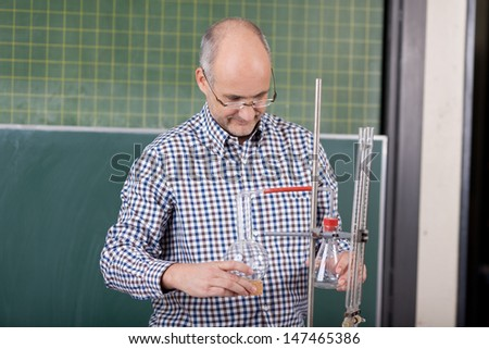 Attractive mature male teacher preparing a chemistry experiment for the class standing in front of a blackboard with a retort stand and glassware - stock photo
