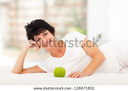 attractive mature woman lying on bed with a green apple in front