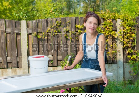 Attractive mature woman posing during furniture painting outdoors