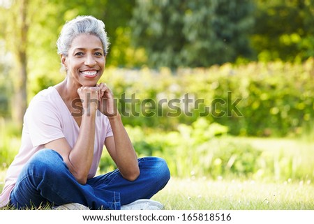 Attractive Mature Woman Sitting In Garden - stock photo
