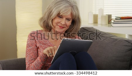 Attractive mature woman tablet smiling - stock photo
