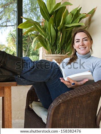 Attractive mature woman with her feet up on a table, sitting in a home conservatory with large glass windows and a green garden, reading a book and relaxing indoors, smiling. - stock photo
