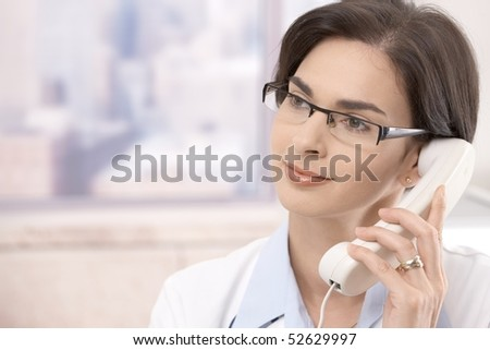 Attractive mid-adult caucasian female doctor talking on landline phone, looking away. - stock photo