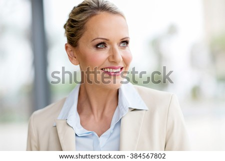 attractive mid age businesswoman looking outside window - stock photo