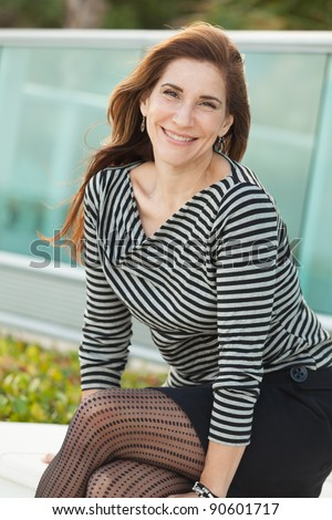 Attractive middle age woman outdoors in a metropolitan downtown urban setting. - stock photo