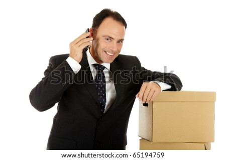 Attractive middle aged caucasian businessman against the storage boxes talking in cell phone . Studio shot. White background. - stock photo