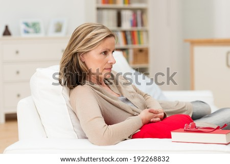 Attractive middle-aged depressed worried woman relaxing at home lying on a sofa staring straight ahead with a serious expression - stock photo