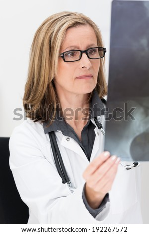 Attractive middle-aged doctor or radiologist wearing glasses standing examining an x-ray film in a hospital as she checks on progress or makes a diagnosis - stock photo