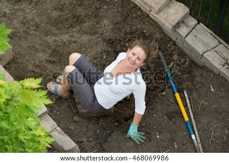 Attractive middle-aged female gardener working in her backyard doing maintenance on the flowerbeds sitting on the newly dug over soil smiling up at the camera