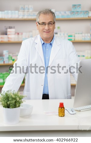 Attractive middle-aged male pharmacist wearing glasses standing behind a counter in the pharmacy ready to assist a patient with a pensive smile - stock photo