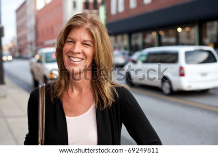 Attractive middle-aged woman downtown in the city. - stock photo