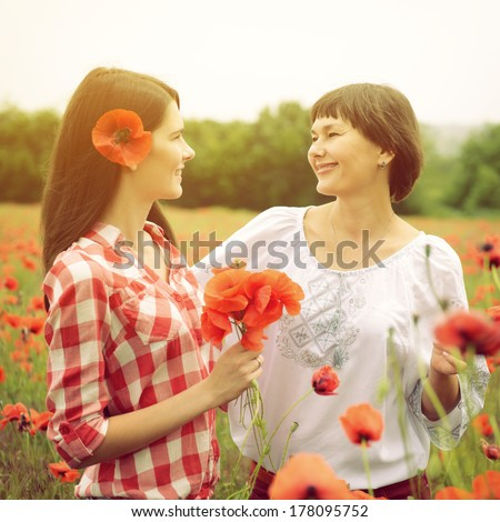 Attractive middle-aged woman has fun on a poppy field with her, summer outdoor. Image toned. - stock photo