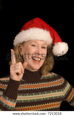 Attractive middle-aged woman in a santa hat and seasonal sweater with an idea and waving a finger over a black background - stock photo