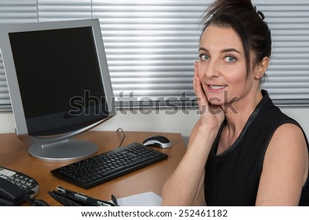 Attractive middle aged woman in business outfit sitting in her office