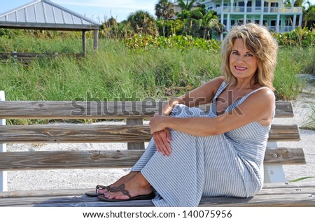 Attractive Middle Aged Woman Sitting on a Bench - stock photo
