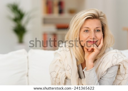 Attractive middle-aged woman sitting on a sofa at home daydreaming resting her chin on her hand staring to the side with a dreamy thoughtful expression - stock photo
