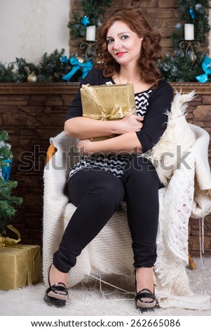 Attractive middle aged woman sitting on the chair with a gift box - stock photo