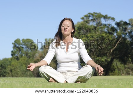 Attractive middle aged woman sitting relaxed with closed eyes in park meditating, isolated with trees and sky as blurred background and copy space. - stock photo