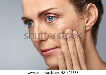 Attractive middle aged woman touching her cheek skin, mature beauty concept