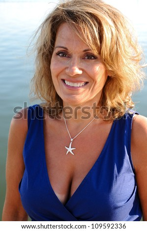 Attractive Middle Aged Woman Wearing A Blue Summer Dress - stock photo