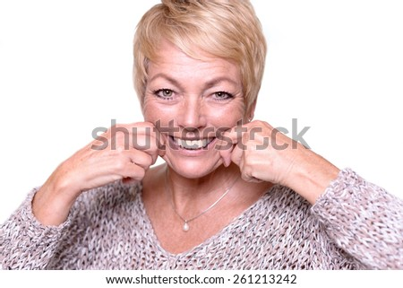 Attractive middle-aged woman with short blond hair trying to reverse the signs of aging by pulling on her cheeks with her hands to give herself a temporary face lift - stock photo