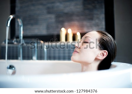 Attractive Mixed Asian Female enjoying the bath with candles - stock photo
