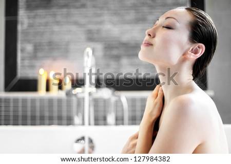 Attractive Mixed Asian Female washing hair while enjoying bath - stock photo