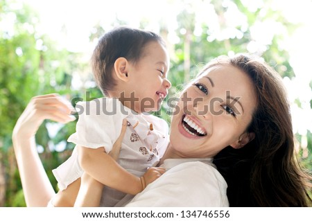 Attractive mixed female lifestyle spending time with child laughing - stock photo