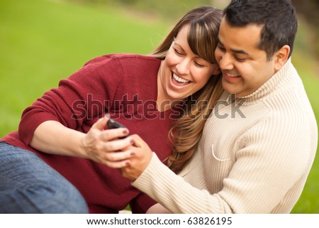 Attractive Mixed Race Couple Enjoying Their Camera Phone in the Park. - stock photo