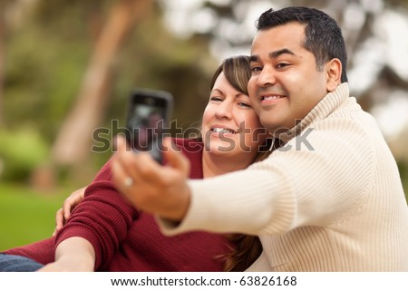 Attractive Mixed Race Couple Taking Self Portraits in the Park. - stock photo