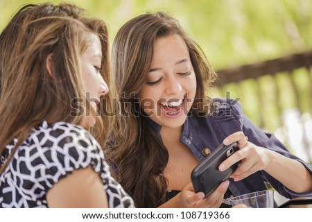 Attractive Mixed Race Girls Smiling and Talking While Working on Smart Mobile Phone and Tablet Computer. - stock photo