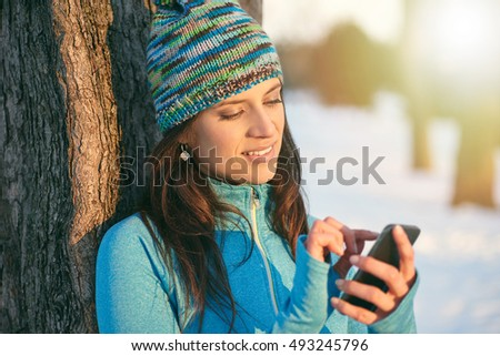 Attractive mixed race woman using a mobile phone in the park at