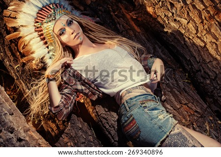 Attractive modern girl in style of the American Indians. Western style. Jeans fashion. Tattoo. - stock photo