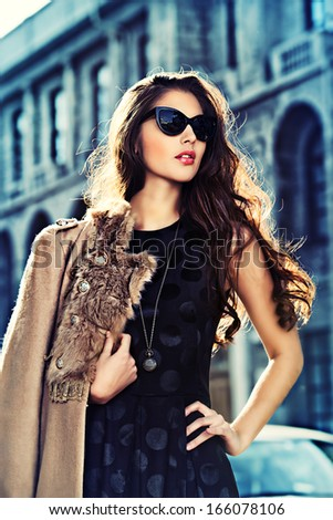 Attractive modern woman standing on the city street.