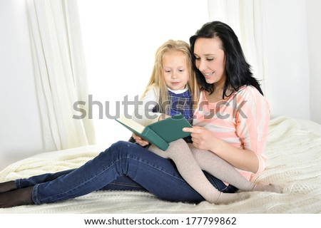 attractive mother and adorable blond daughter reading a book at home - stock photo