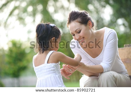 Attractive Mother and daughter spending time together in the park - stock photo